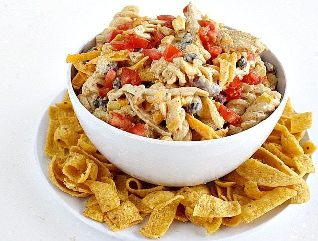 Fiesta Ranch Chicken Pasta Salad is full of fresh southwestern flavors with black beans, corn, cheese and tomatoes. Hearty chicken salad recipe topped with Fritos!