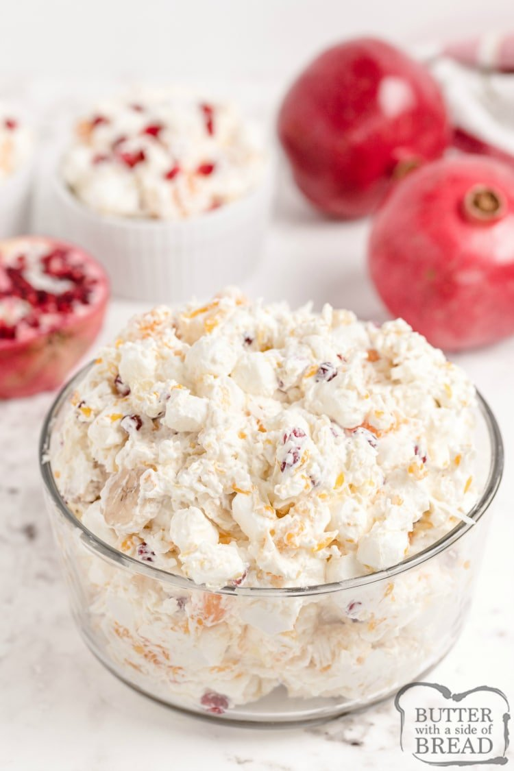 Fruit salad with coconut, pomegranate, bananas, oranges and whipped cream