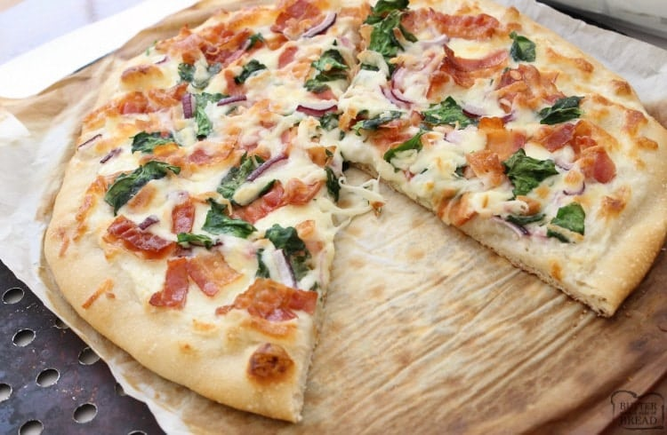 Bacon Alfredo Pizza baked fresh and full of flavor! Easy pizza recipe made with Alfredo sauce, bacon, red onion, spinach and lots of mozzarella cheese.