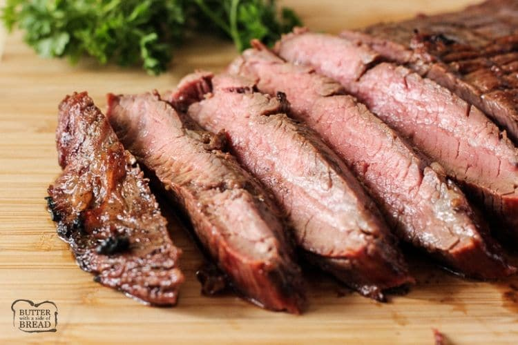 sliced grilled flank steak on a wooden cutting board