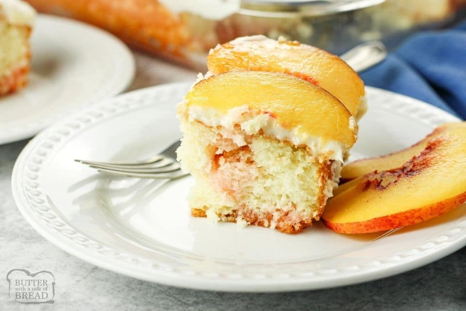slice of poke cake with fresh peach slices on top