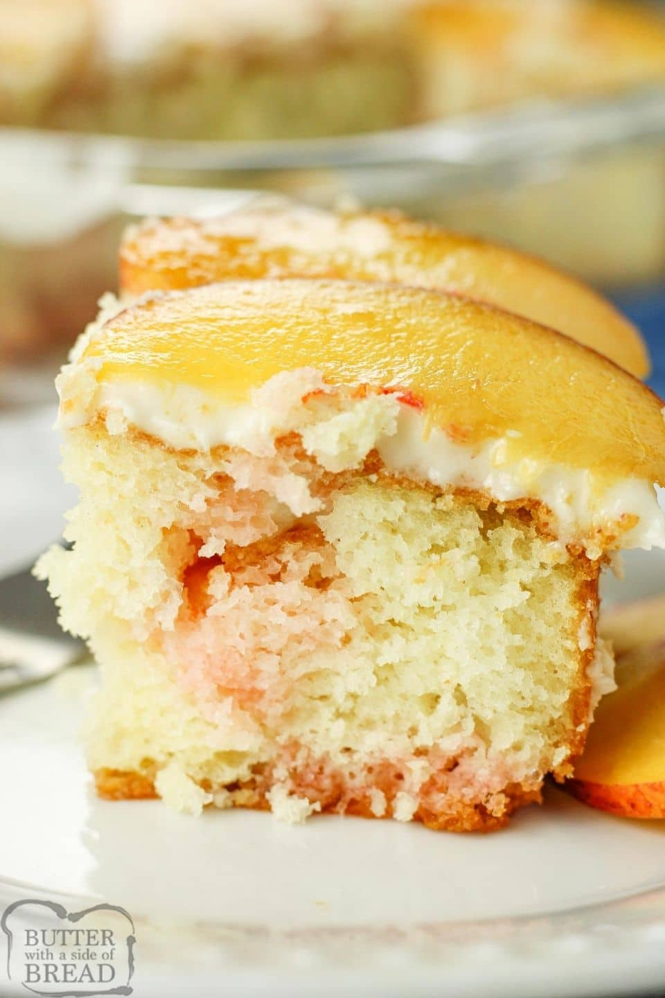 slice of peach poke cake topped with fresh peach slices