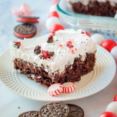 Peppermint Oreo Poke Cake uses a cake mix, cookies & cream pudding, whipped cream, Oreos & peppermint candies for a deliciously festive holiday cake! Easy Christmas cake recipe with peppermint cookie flavors.