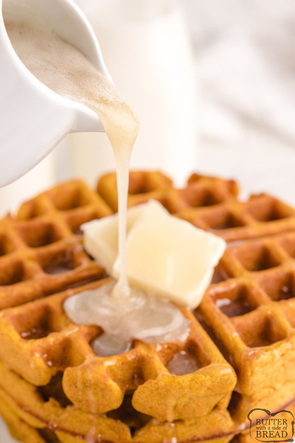 Buttermilk syrup being poured over pumpkin waffles